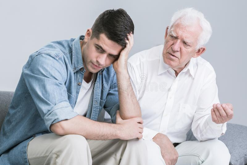 Troubled man talking with father royalty free stock photography
