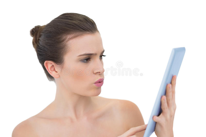 Troubled Natural Brown Haired Model Using A Tablet Pc Royalty Free Stock Photos