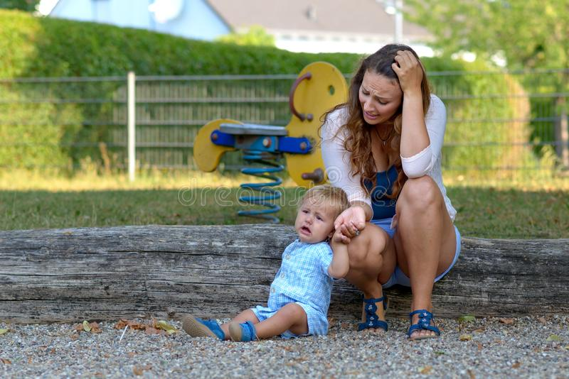 Troubled stressed young mother with her baby son. Troubled stressed young mother with her crying unhappy baby son outdoors in a playground royalty free stock images