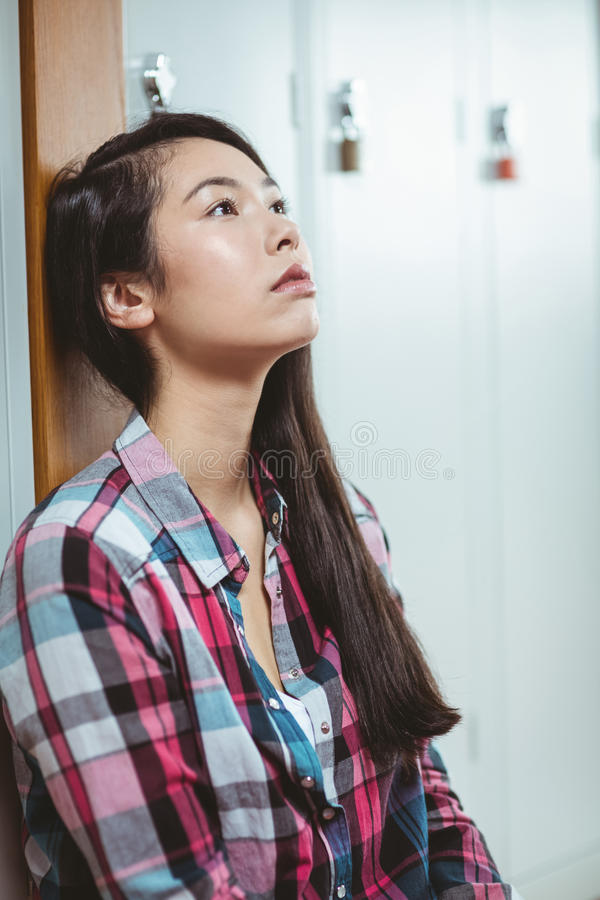 Troubled student sitting and looking up stock image