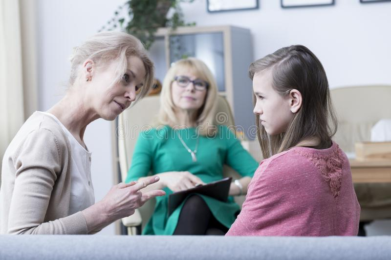 Troubled teenage girl. Worried mother talking to troubled teenage girl during psychological visit stock photography