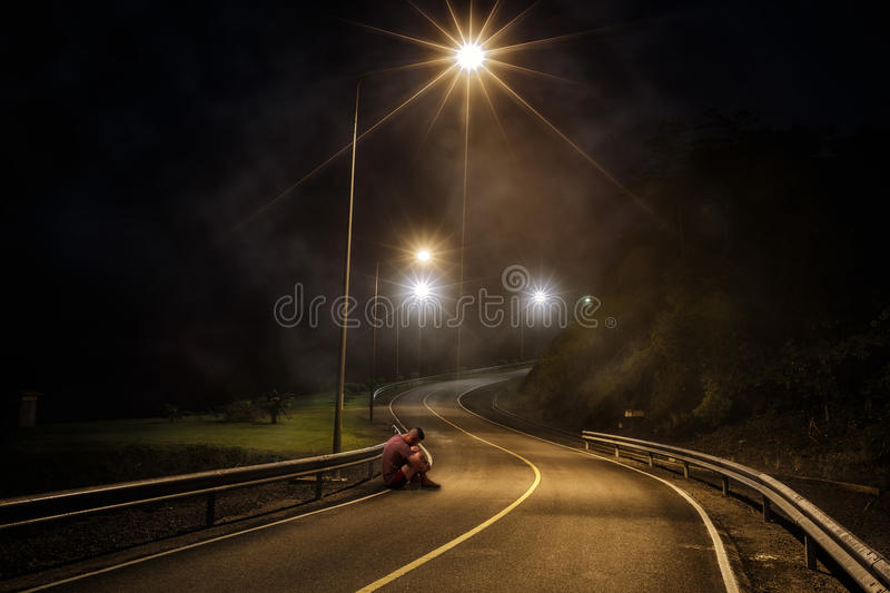 Troubled teenager with hidden face sitting in the night street royalty free stock photography