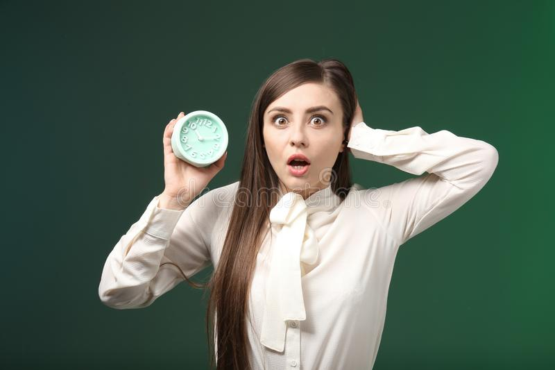 Troubled woman with alarm clock on color background. Time management concept stock images