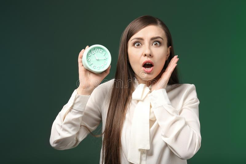 Troubled woman with alarm clock on color background. Time management concept royalty free stock photography
