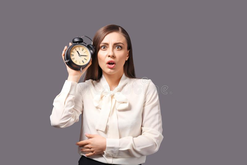 Troubled woman with alarm clock on grey background. Time management concept stock photos