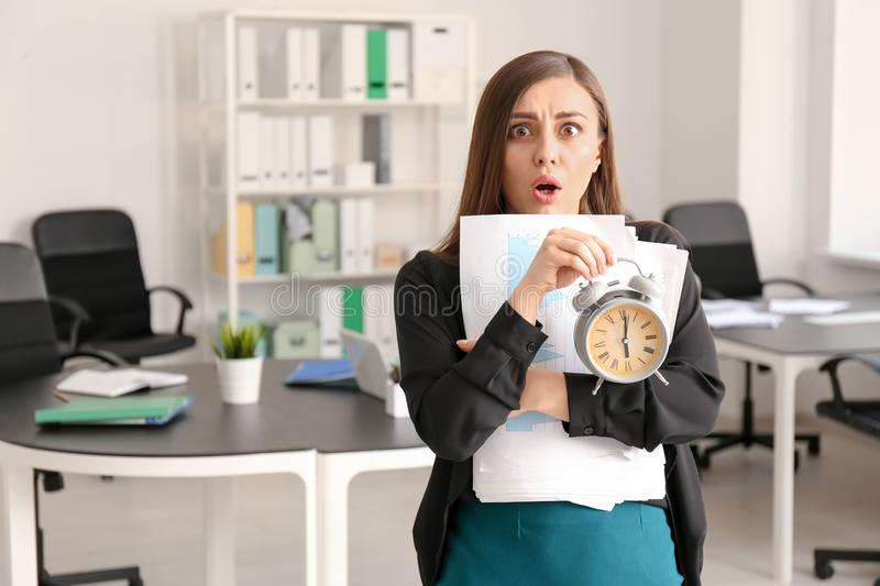 Troubled woman with alarm clock in office. Time management concept royalty free stock photography