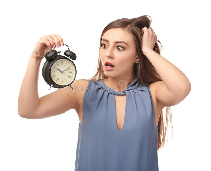 Troubled woman with alarm clock on white background. Time management concept stock photography