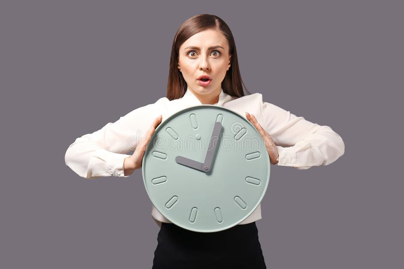 Troubled woman with clock on grey background. Time management concept stock image