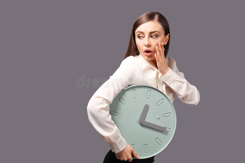 Troubled woman with clock on grey background. Time management concept stock images