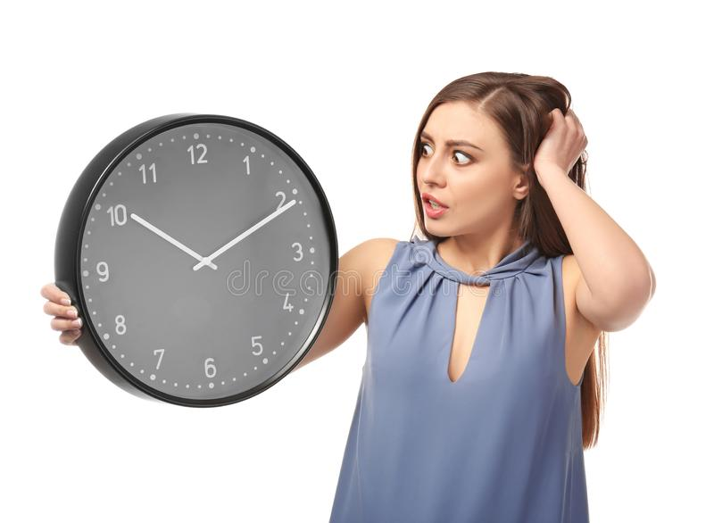 Troubled woman with clock on white background. Time management concept stock image