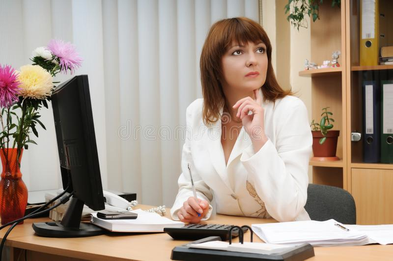 Troubled woman holding pen above calculator royalty free stock photos