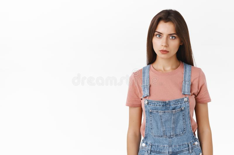 Troubled and worried, annoyed serious-looking girl gonna exploud from anger, standing pissed and stare camera ready to. Punch someone in face, pose over white stock image