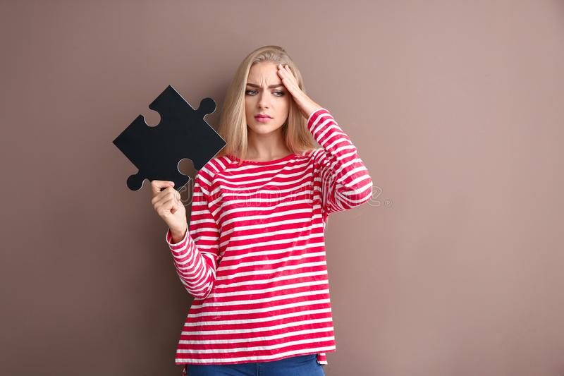 Troubled young woman with piece of puzzle on color background stock image