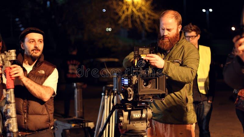 Troupe cinematografica su posizione, tiro di notte Cinamatographer con la macchina fotografica 4k fotografia stock