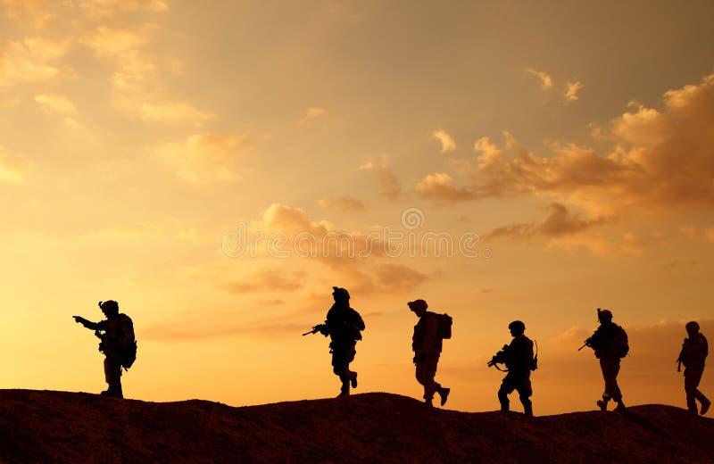 Troupes et hélicoptère militaires sur le chemin au champ de bataille image stock