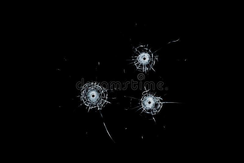 Trous de balle triples en verre cassés en verre d'isolement sur le noir image stock