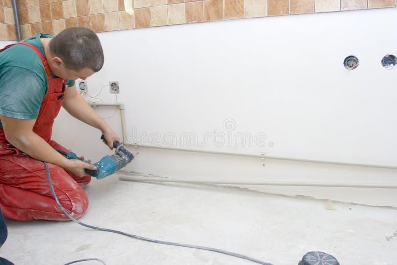 Trous de perçage pour les conduites d'eau de fixation image stock