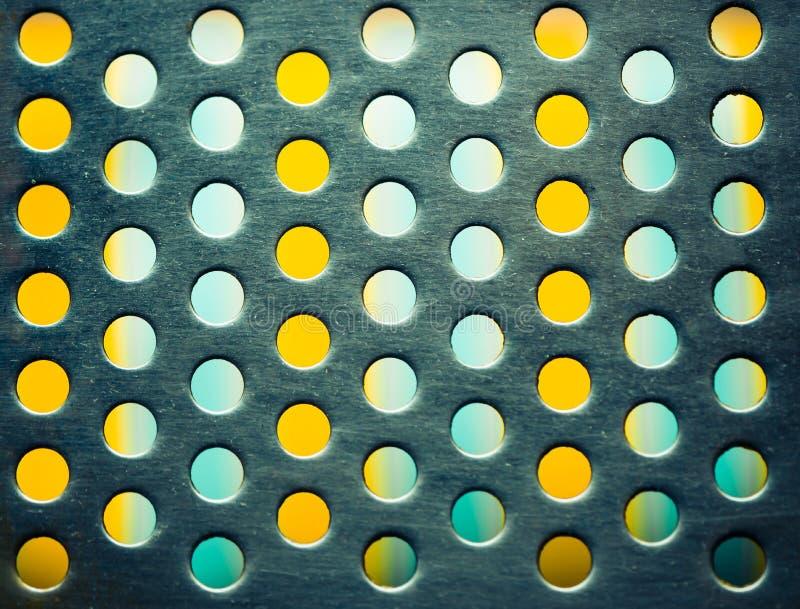 Trous métalliques sur le fond coloré photo stock