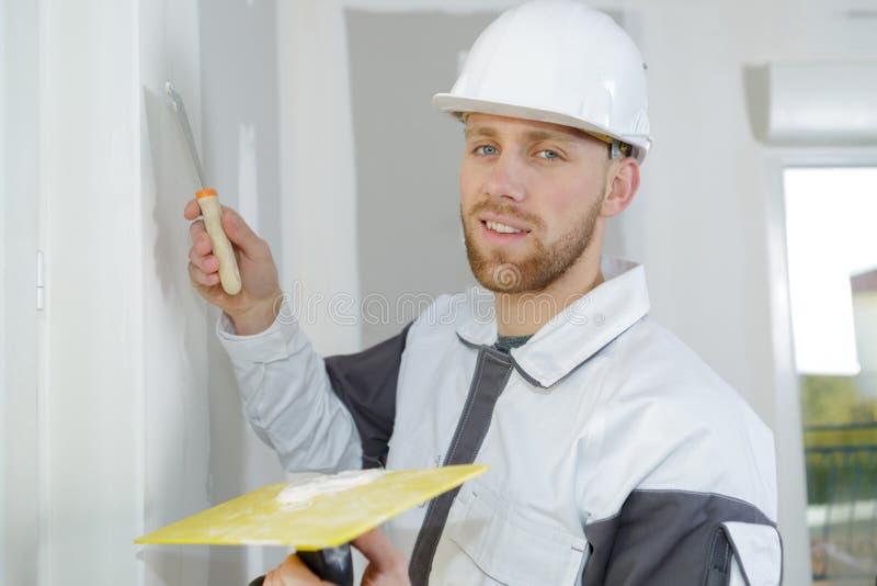 Trous remplissants de constructeur sur le mur photos libres de droits