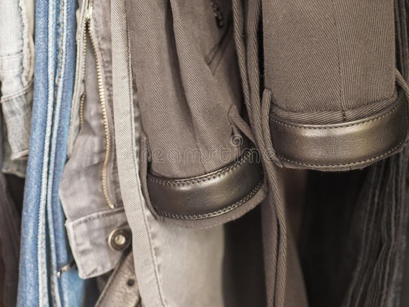 Trousers in a closet. Many male trousers hanging in a closet stock image