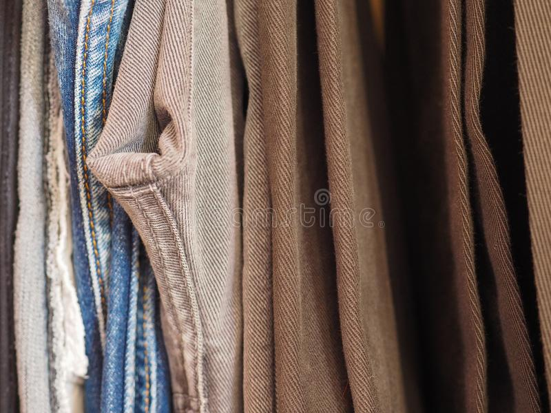 Trousers in a closet. Many male trousers hanging in a closet royalty free stock photos
