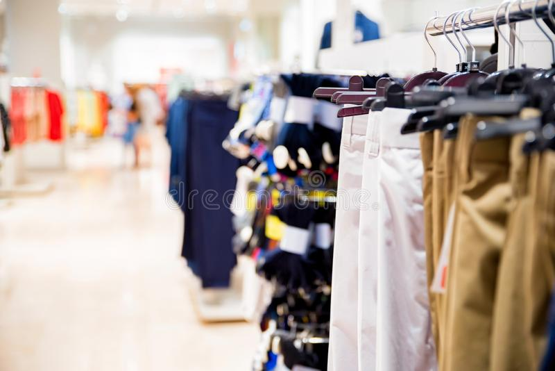 Trousers hang on rails in modern clothes shop. View of clothes shop interior with various pants on hanging rail royalty free stock images