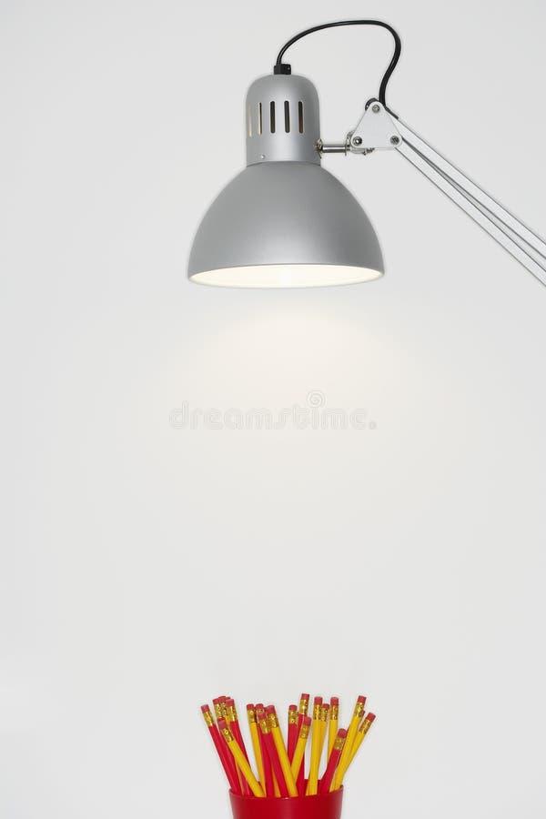 Trousse d'écolier au-dessous d'une lampe photo libre de droits