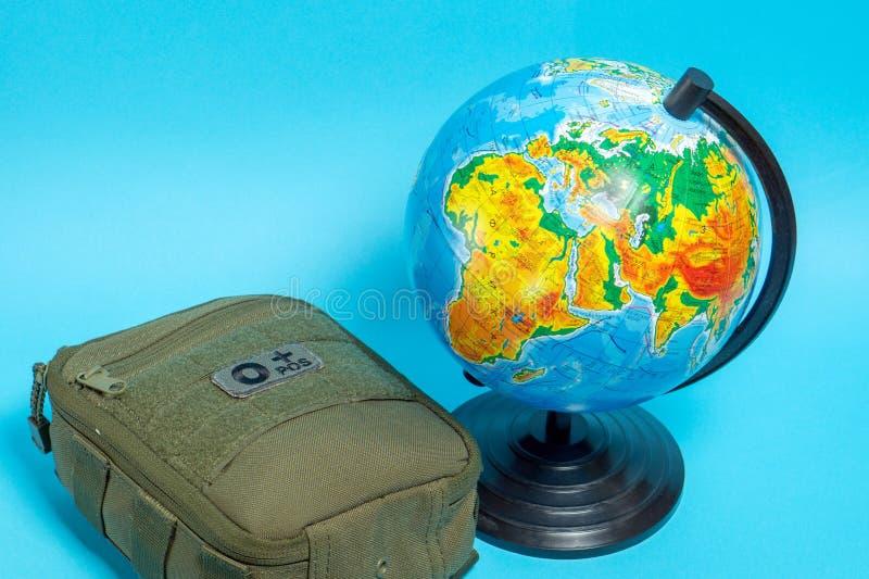 Trousse de premiers soins verte à côté du globe sur un fond bleu photo libre de droits