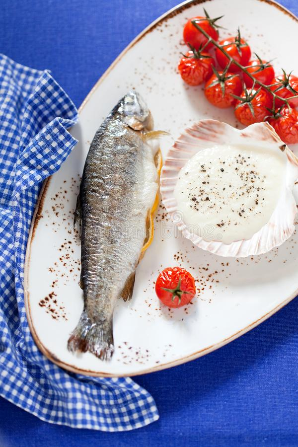 Trout baked with onion sauce and cherry tomatoes royalty free stock photos