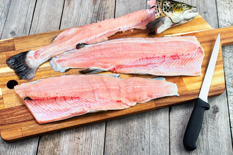 Trout fillets. On cutting board with filleting knife stock photo