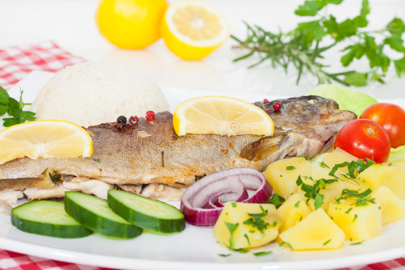 Trout fish baked with potatoes stock photography
