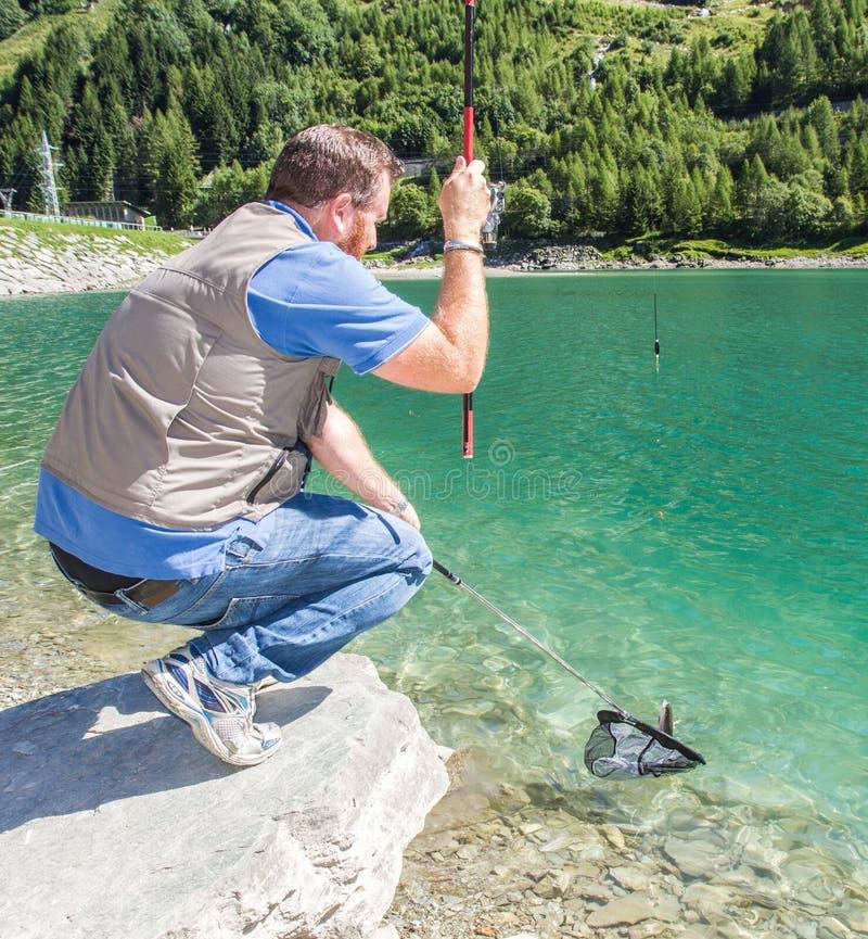 Trout-fishing on mountain lake royalty free stock photos