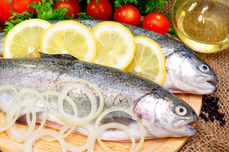 Trout. With lemon and fresh vegetables stock image
