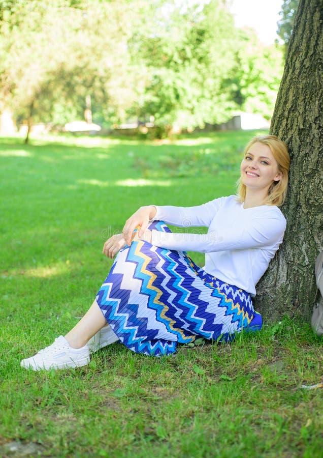 Trouvez l'endroit paisible en parc Donnez-vous la coupure et appréciez les loisirs La fille s'asseyent sur le maigre d'herbe sur  images libres de droits