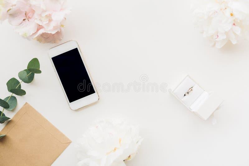 Trouwring in witte giftdoos op achtergrond van bloemen en telefoon Hoogste mening stock fotografie