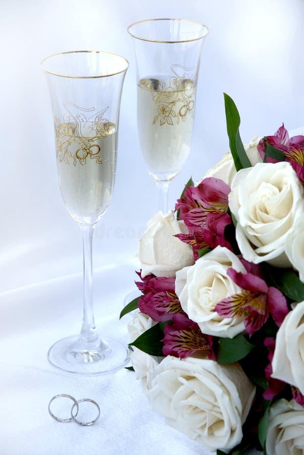 Trouwringen, champagne en bloemen stock afbeeldingen
