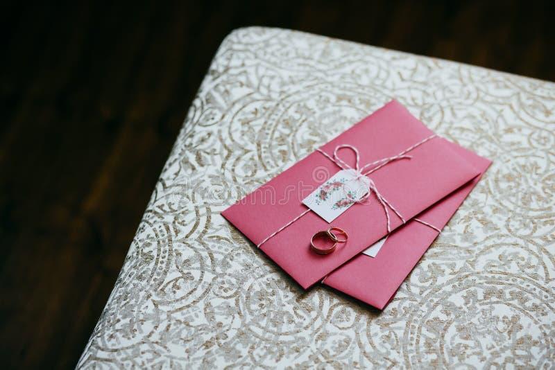 Trouwringen die op roze uitnodigingskaart liggen Huwelijksvoorbereidingen en decoratie Huwelijkskaart door bruidegom en bruid wor stock afbeeldingen