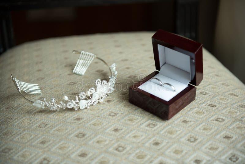 Trouwringen in een bruine doos en een kroon stock afbeeldingen