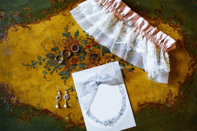 Trouwringen en bruids kouseband op de uitstekende lijst royalty-vrije stock afbeelding