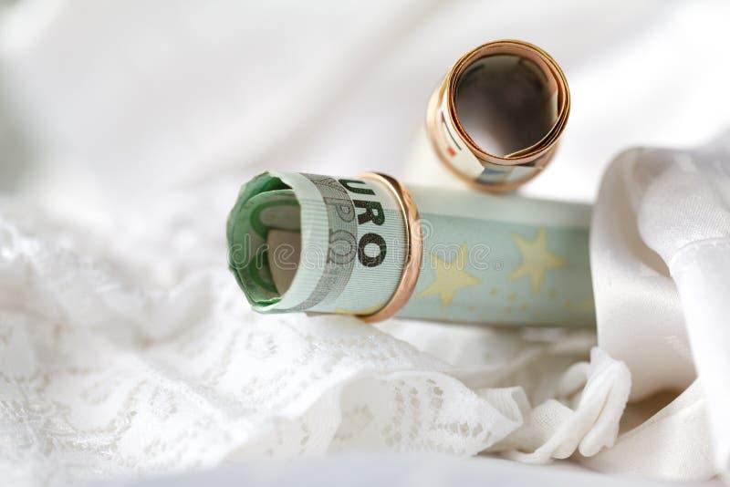 Trouwringen en geld op een witte bruids lingeryachtergrond stock foto