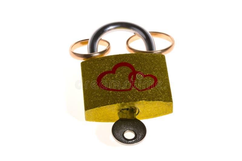 Trouwringen en hangslot dat op een witte achtergrond worden geïsoleerde Het concept huwelijk of huwelijk De dag van de valentijns stock foto