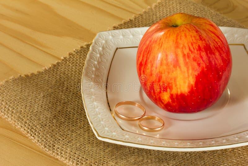 Trouwringen en rood rijp Apple royalty-vrije stock foto's