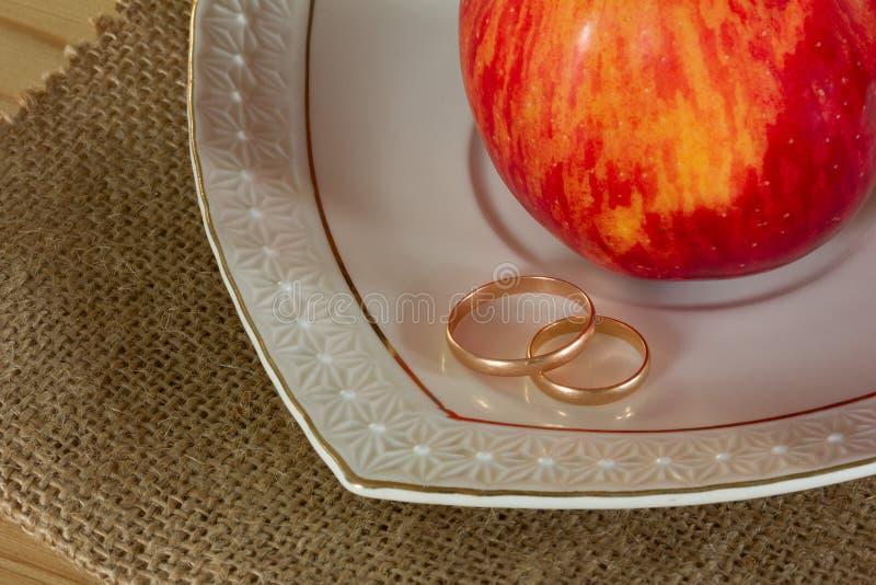 Trouwringen en rood rijp Apple royalty-vrije stock fotografie