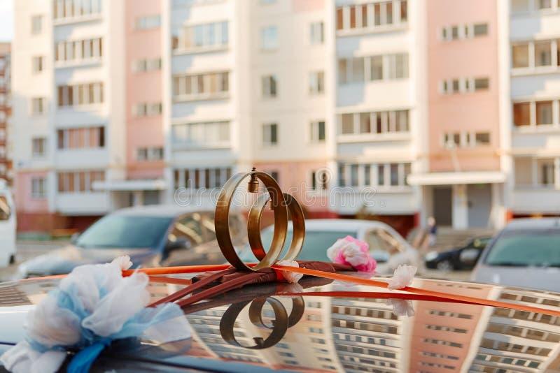 Trouwringen met klokken op het dak van de auto, tegen de achtergrond van stedelijke gebouwen Traditionele Russische decoratie van royalty-vrije stock fotografie