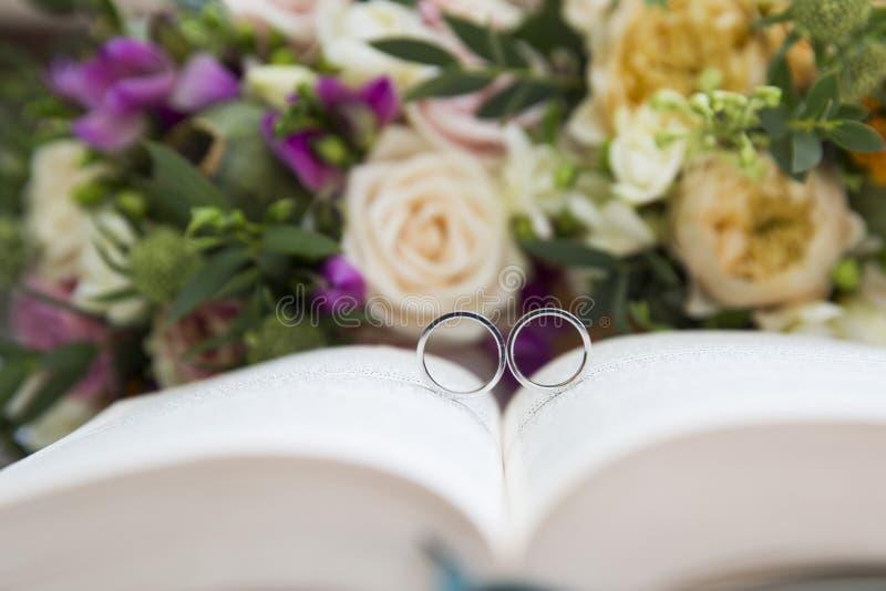 Trouwringen op boek en bloemen stock afbeelding