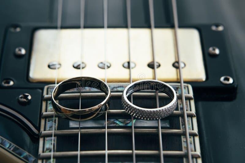 Trouwringen op de koorden van de gitaar stock foto