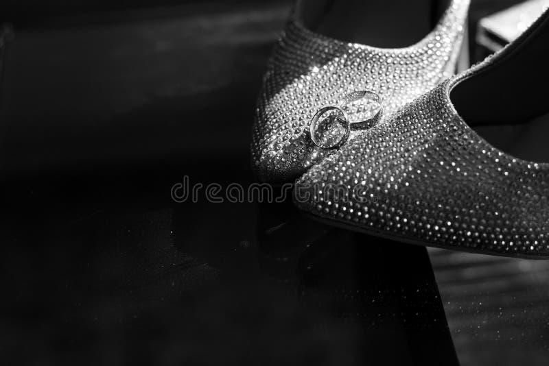 Trouwringen op de schoenen van de bruid Huwelijk decor De schoenen van de bruid `s De schoenen en de ringen van de huwelijksbruid royalty-vrije stock afbeeldingen