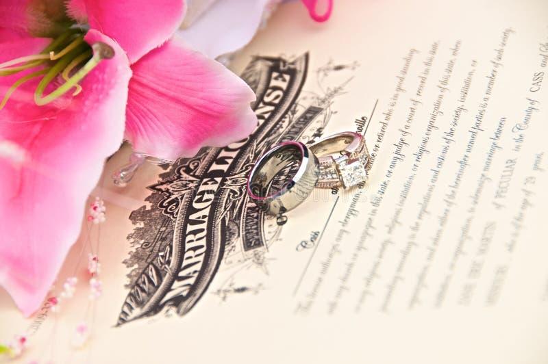 Trouwringen op de Vergunning van het Huwelijk stock afbeelding