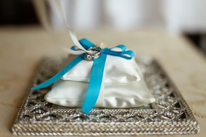 Trouwringen op een kussen met blauw lint stock afbeelding