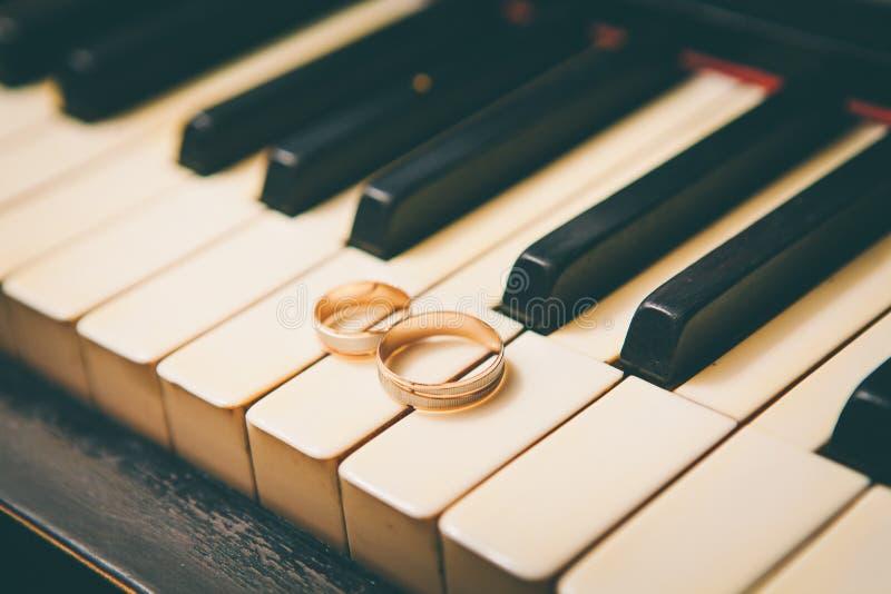 Trouwringen op een piano stock foto